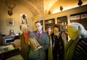 "Irène Chardon, Natalie de Montille, Nathalie Brunel, and Thérèse de Bayser with curator Laurent Ferri holding the book ""Quatuor Evangelia."""