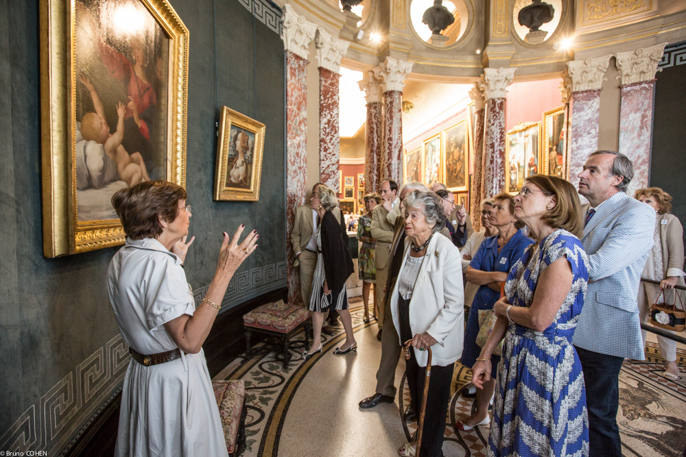 "Guests admire Raphael's ""The Madonna of Loreto"" in the Rotunda as Chief Curator Nicole Garnier describes the restoration process that identified the painting as an original work by the Italian Master"