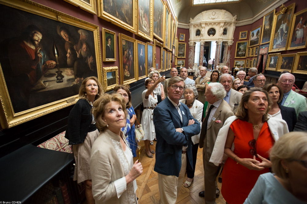 Guests listen attentively as Chief Curator Nicole Garnier describes treasures in the Gallery of Paintings